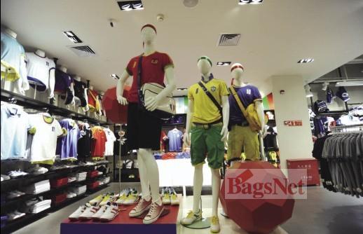 """今夏,足球世界杯席卷全球。作为与世界杯密切相关的运动服饰产业,也无处不在设法利用""""世界杯效应"""",尽全力使自己的品牌价值和利益最大化。而这一切,体现在终端店铺中,无外乎陈列。换言之,目前运动服饰品牌的终端店铺中,恰如远在南非的世界杯赛场一般,正在上演一场关于陈列的主题赛事。  美特斯邦威 红色的足球夸张而夺目,此为亮点所在。带有延续性的场景式陈列法在本季成为一种常见的手法。但在此处,还有提高的空间。虽有彩色球衣作为""""世界杯""""的最好代言元素,但整组模特多达4种色"""